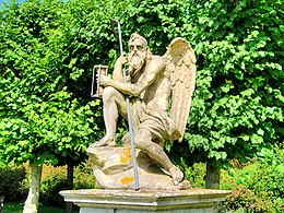 stone statue of winged Father Time with staff and hourglass