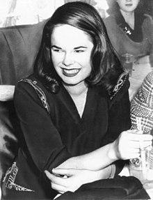 Photographie d'une femme souriante en robe de soirée assise à une table
