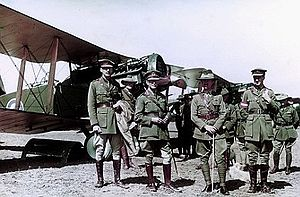 Row of biplanes with four men in military uniforms in the foreground