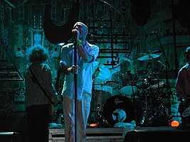 A blue-tinted photograph of musicians in front of an industrial background. From left to right: a long-haired male stands with his back to the camera playing bass guitar, a middle-aged Caucasian male sings into a microphone, a middle-aged Caucasian male plays behind a black-and-silver drum set on a riser, and a guitar player is mostly cropped from the extreme left of the photo.