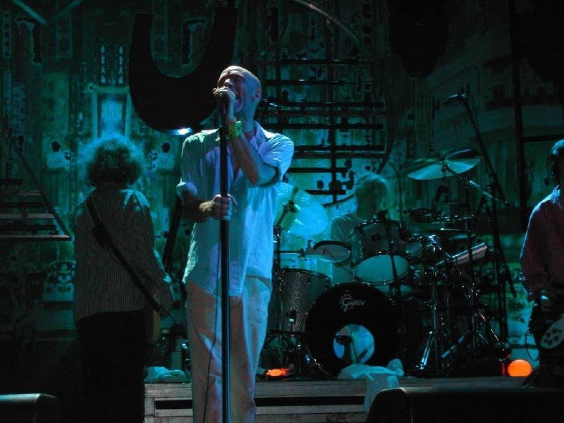 A color photograph of the band R.E.M. on stage