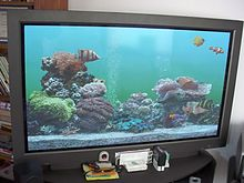 Photograph of a flat panel displaying an aquarium; the aquarium has several fish swimming around, a gravel bottom, and decorative rocks and plants.