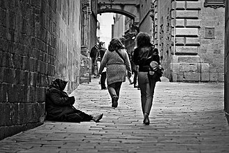 Poverty - A woman begging in an unknown location.