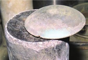 Light-gray standing cylinder. Its top slice has been cut off and slightly shifted aside exposing a darker inside