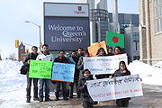 "Students holding placards in front of ""Queen's University"" sign"