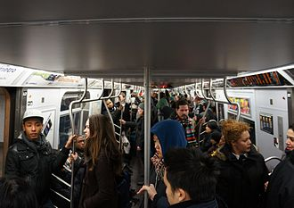 Transportation in New York City - Crowds on an F subway train on a Sunday afternoon.