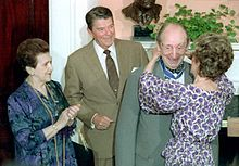 An elderly man is awarded a medal by a woman, she is attaching it around his neck whilst he grins excitedly.