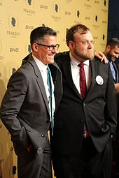 Two men are wearing suits; both are wearing glasses.