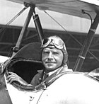 Photogaph of Roderick Burnham seated in a biplane, looking backwards toward the camera, and wearing a period pilot's cap and goggles.