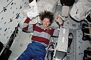 STS-112 Sandra Magnus washes her hair in the middeck of Atlantis