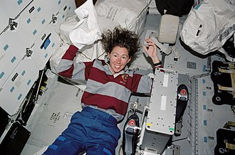 STS-112 - Sandra Magnus washes her hair in the middeck of Atlantis.