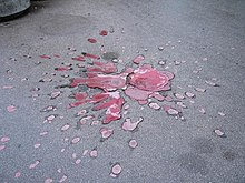 Mortar damage to a road, filled in with red concrete.