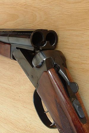 Break action - A view of the break-action of a typical double-barrelled shotgun, with the action open and the extractor visible. The opening lever and the safety catch can also be clearly seen.