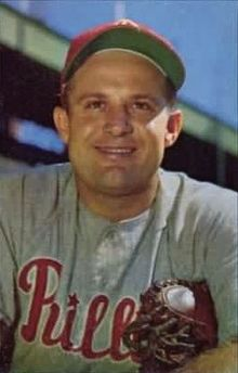 "A man wearing a red baseball cap and a gray baseball jersey with ""Phillies"" written across the chest in red script smiles for the camera while clutching his baseball mitt under one arm."