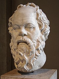 A white marble bust of Socrates with a pug nose and long beard