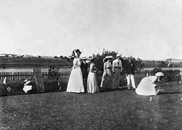 Men and women play lawn bowls. The women, one of whom is about to bowl a ball down the green, wear large hats and long dresses. A scoreboard has been set up next to the group.