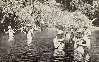Field telephone - Telephone linesmen ford Lunga River during the Guadalcanal Campaign of World War II.