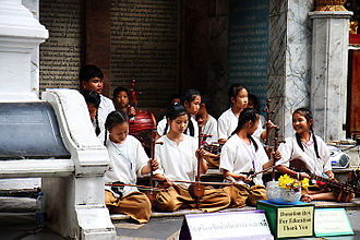 Music of Thailand - Schoolgirls and boys playing khrueang sai in front of a temple