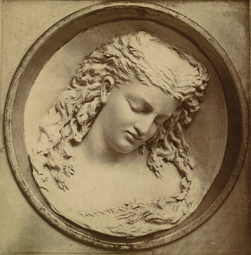 Photograph of a sculpture of a young woman's head and shoulders with intricate flowing hair, her face tilted to the bottom-right while her eyes appear closed—as carved in a tub of butter