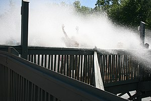 Timberwolf Falls - Spectators being hit and soaked in the Splash Zone by a wave created as a boat makes it to the bottom of the drop.