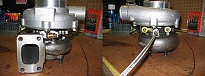 Turbocharger - On the left, the brass oil drain connection. On the right are the braided oil supply line and water coolant line connections.