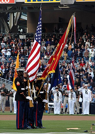 "Flag of the United States Marine Corps - A U.S. Marine color guard dips the U.S. Marine Corps flag for a playing of ""The Star-Spangled Banner"" in April 2005."