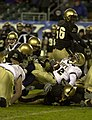 US Navy 031206-N-9693M-522 Navy fullback Bronston Carroll is tackled by a group of Army defenders during the 104th Army Navy Game.jpg