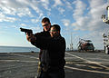 US Navy 090131-N-6138K-001 Electrician's Mate 3rd Class Joseph Roverano teaches Personnel Specialist 1st Class Carlene Mart proper gun control during live-fire small-arms qualifications.jpg