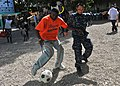 US Navy 100727-N-1531D-578 Boatswain's Mate Seaman Zhijian Chen, from Hong Kong, plays soccer with Haitian children during a Continuing Promise 2010.jpg