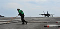 US Navy 110909-N-OY799-247 Aviation Boatswain's Mate (Equipment) 3rd Class Aaron Rutledge retracts the arresting wire after an F-A-18F Super Hornet.jpg