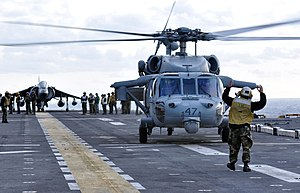US Navy 120202-N-EC658-012 A landing signalman enlisted prepares an MH 60S Sea Hawk helicopter from Helicopter Sea Combat Squadron (HSC) 28 for tak.jpg