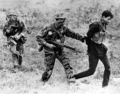 US Navy SEALs Terry Sullivan, left, and Curtis Ashton with a captured Viet Cong in the My Tho area, 1969.PNG