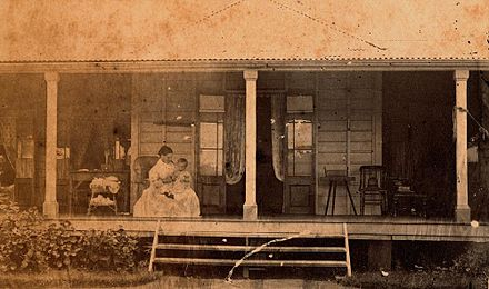 Winifred Rawson tending her son on the veranda of The Hollow, near Mackay, Queensland, ~1873