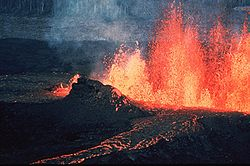 A volcano is the release of stored energy from below the surface of Earth originating in radioactive decay and gravitational sorting in the Earth's core and mantle of energies left over from its formation