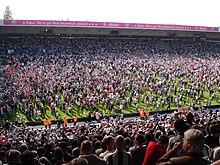 Photo des gradins d'une foule envahissant le terrain de football.