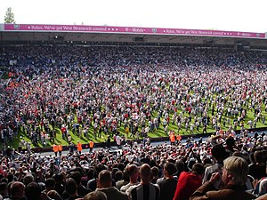 "Association football culture - Supporters of West Bromwich Albion invade the pitch after the final whistle to celebrate the ""Great Escape"" of avoiding relegation on the last day of the 2004–05 season."