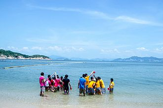 Orientation camps in Hong Kong - Students playing with each other at the beach.