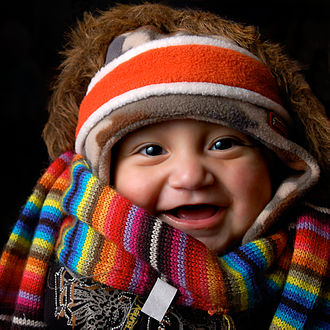 Clothing - A baby wearing many items of winter clothing: headband, cap, fur-lined coat, scarf and sweater.