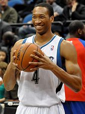 Wesley Johnson smiling and griping a basketball, standing upright