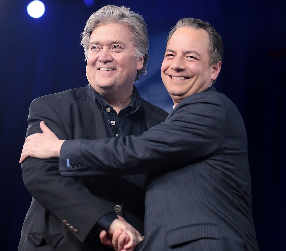 White House Chief of Staff Reince Priebus and WH Chief Strategist Steve Bannon shake hands at 2017 Conservative Political Action Conference (CPAC)
