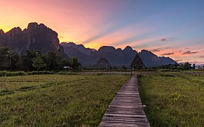 Wooden walkway leading to a hut with straw roof at sunset with colorful sky in Vang Vieng Laos.jpg