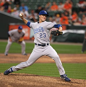 A young man in a blue cap and gray baseball uniform with blue lettering on the chest, including the number 23, pitches a baseball right-handed.