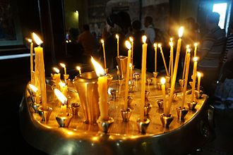 Votive candle - Orthodox churches use long, thin candles, which are placed in round containers.