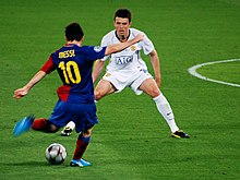 A man wearing a blue-and-red football shirt prepares to kick a football, while a man in a white shirt looks on.