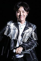 J-Hope dancing against a black sky. A mic is in his right hand.