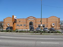 A large brick building behind black gates with and a parking lot with several parked cars