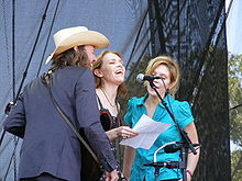 A man and two women crowded around a microphone and singing.  The man is on the left and wearing a dark blue suit and a white cowboy hat. Welch, in the middle, is wearing a black dress, and the woman on the right is wearing a green dress.
