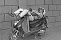 A Man is sleeping on his motobike.jpg