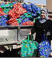 A member of the Ramadi Widows Outreach Assistance Program distributes food packages to about 500 residents during an Iraqi police-led humanitarian assistance event at the business center in the Anbar province 100829-A-CE832-004.jpg