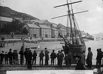 Men standing on a quay with a sailing ship in the background